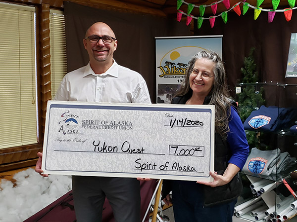 Anthony Rizk presenting the Spirit of Alaska 2020 Sponsorship Check to the Yukon Quest Director Marti Steury